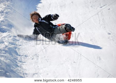 Boy Falling While Sledding Down The Hill