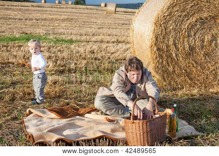 Young Man And Two Little Boys Making Picnic On Hay Field