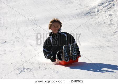 Boy Sledding Down The Hill