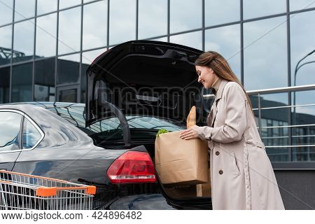 Young Housewife Putting Shopping Bag Into Car Trunk On Parking