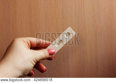 Woman Is Hand Holding Positive Pregnancy Test On A Light Background. Motherhood, Pregnancy, Happines