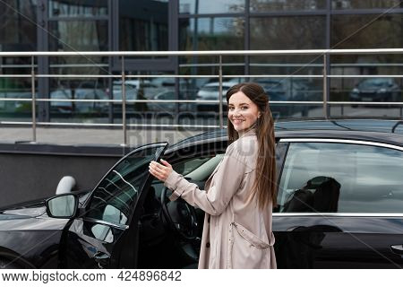 Pleased Woman Smiling At Camera While Opening Door Of Car