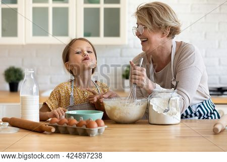 Little Girl Having Fun Cooking With Granny In Kitchen.