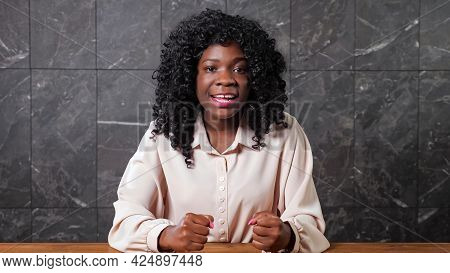 Young Black Woman Worker With Long Loose Curly Hair Talks Gesticulating And Sitting At Brown Wooden