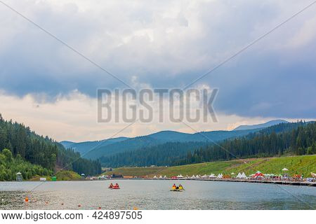 Entertaiment Of Voda Club On The Pond Among Carpathian Mountains. Rental Boats For Lake Tour. Carpat