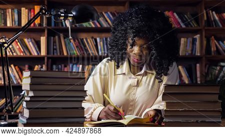 Young African-american Woman Writes In Paper Notebook Near Stacks Of Books And Lamp Sitting At Table