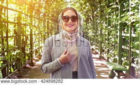 Woman In Headscarf And Sunglasses Smiling In Garden Arch, Sunlight