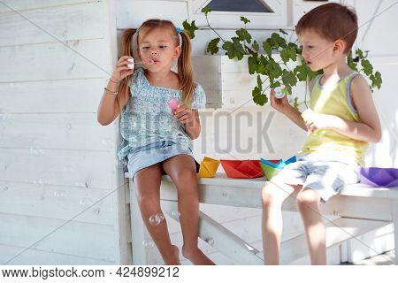 caucasian brother and sister sitting on a porch playing with paper boats, making soap bubbles