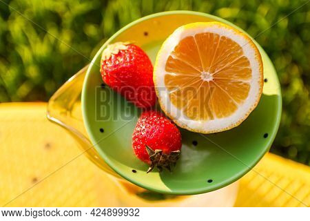 Defocus Close-up Saucer With Lemon And Two Strawberry Standing On Glass Jug Of Lemonade On Yellow Bo