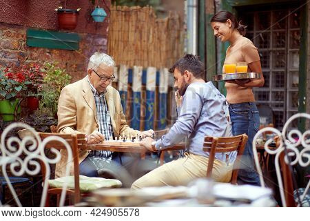 two men, young and senior, playing chess in outdoor cafe, thinking, with waitress beside watching and smiling. selective focus image with copy space