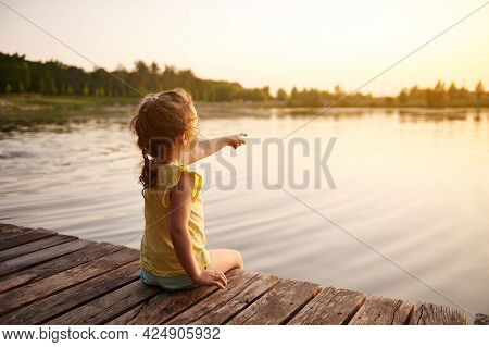 Rear View Of A Cute Baby Girl Sitting On A Wooden Pier At The Lake And Pointing Her Finger At A Beau