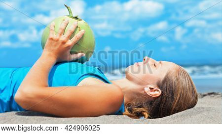 Fit Woman Exercising With Young Coconut On Ocean Beach. Sportive Woman Doing Workout. Fitness Woman