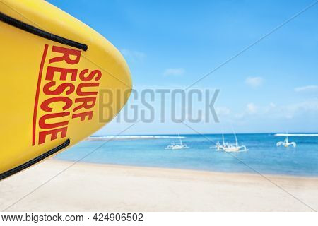 Life Saving Yellow Board With Surf Rescue Sign. Lifeguards Stand On Duty, Look At Blue Sea. Swimming