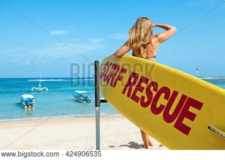 Life Saving Yellow Board With Surf Rescue Sign. Young Lifeguard Woman Stand On Duty, Look At Blue Se