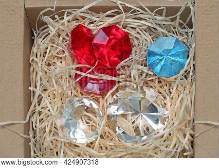 Shiny Colorful Diamonds In Cardboard Box With Paper Protection