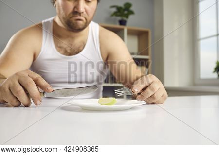 Sad Chubby Man Whos Sticking To Strict Diet Looking At Tiny Piece Of Apple For Lunch
