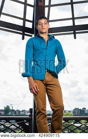 Dressing In A Blue Shirt, Brown Pants, A Young Attractive Guy Is Standing In The Front Of The Broad
