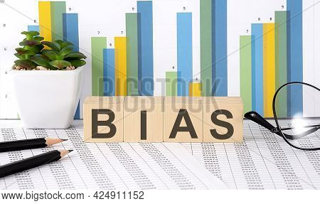 Bias Word Written On Wood Block With Chart, Glasses And Pencils