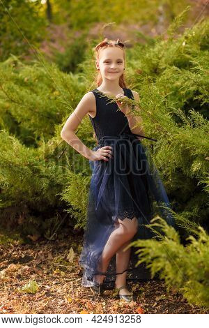 A Beautiful Little Red-haired Girl In A Blue Dress Walks In Nature In A City Park On A Warm Summer D