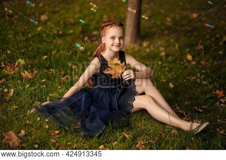 A Beautiful Little Red-haired Girl In A Blue Dress Lies On The Grass With A Yellow Large Maple Leaf