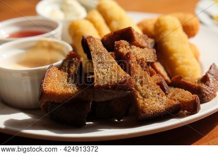 Fast Food, Fresh Beer Snacks Assortment. Fried Rye Bread Croutons And Cheese Sticks With Sauces, Bee