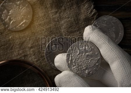Numismatics. Old Collectible Coins Of Silver On The Table.  A Collector In Special Gloves Holds An O
