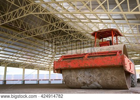 Low Angle View Of Soil Compactor Roller Inside Of Building Structure In Construction Site.
