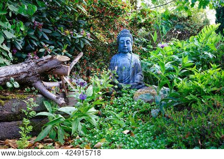 Sitting Buddha Figurine Mediating, Situated In Garden Of Green Leaves And Small Flowers With Rocks A