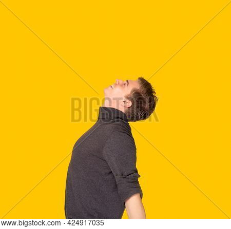 Carefree Man Enjoying In Freedom With Arms Outstretched Standing Over Yellow Background Studio Shot