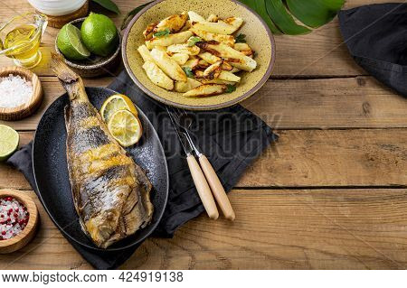 Baked Sea Bass Or Lingcod Fish With Potatoes On The Wooden Table, Copy Space For Text