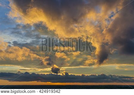 Spectacular Yellow-orange Sunset Over The Forest. The Sun Sets, Illuminating The Plump Clouds With R