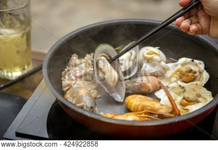 Cooking Grill Oyster And Seafood Manu With Electric Hot Pan And Keep With Chopstick On Dinner Table