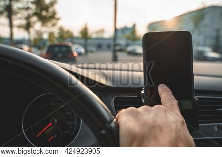 Hand Of Driver Touches Smartphone Display While Driving Car