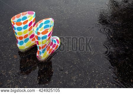 Colorful Polka Dot Boots In Rain Puddle With Rain Drops