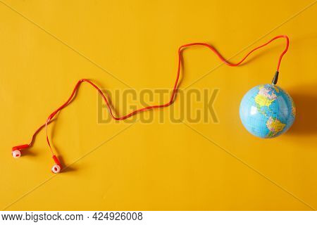 Red Wired Earbuds Are Connected To A Small Globe. The Concept Of Broadcasting, Webcasting, Podcastin