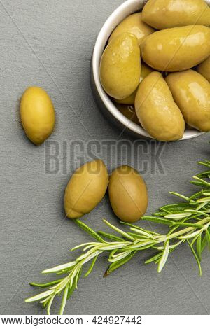 Green Olives. Bella Di Cerignola Italian Olives. Colored Olives And A Sprig Of Rosemary Lie On A Bla