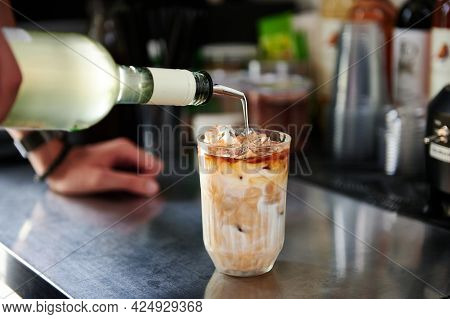 Close-up Of Barista Preparing A Refreshing Caffeinated Iced Drink, Pouring A Liquid Cocktail In A Gl