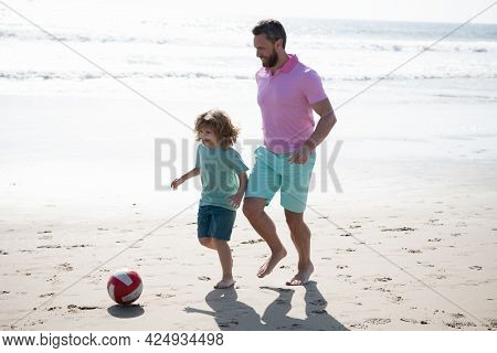 Father And Son Play Soccer Or Football On Beach. Daddy With Kid Boy On Summer Day.