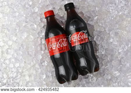 IRVINE, CALIFORNIA - 26 JUNE 2021: A bottle of Coca-Cola and Coca-Cola Zero in a bed of Ice.