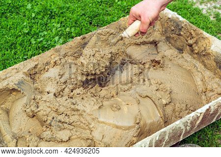 Mix The Cement With Sand And Water With A Trowel. Builder Is Hand With A Trowel During Work.