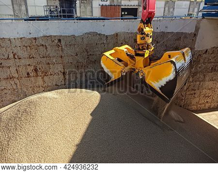 A Crane With A Manipulator Bucket Loads Coal Onto A Dry Cargo Ship In The Port. Loading And Unloadin