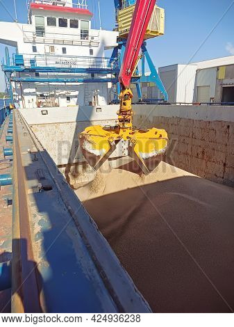 A Crane With A Manipulator Bucket Loads Wheat Onto A Dry Cargo Ship In The Port. Loading Bulk Cargo