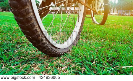 The Flatten Tire Bicycle Is On The Green Field