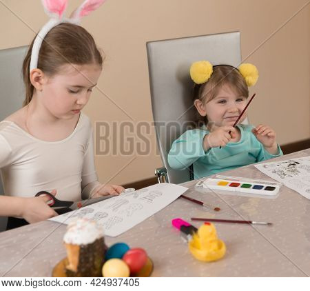 Funny Little Girls In Funny Headbands With Yellow Pompoms And Pink Rabbit Ears Paint With Paint Brus