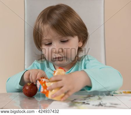 A Three-year-old Girl In A Turquoise Blouse Is Enthusiastically Looking At A Yellow Chicken-a Stand