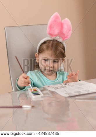 A Little Girl In A Cute Headband With Pink Bunny Ears Draws With A Brush With Watercolor Paints