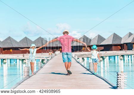 Little Girls With Dad On Wooden Jetty Near Water Bungalow At Exotic Resort