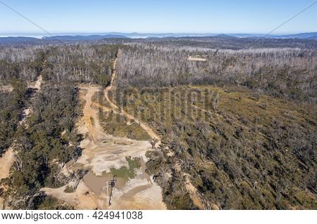 Drone Aerial Photograph Of Flood Water On A Dirt Road In A Forest In Regional Australia