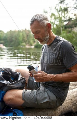 Middle Aged Caucasian Man Distillating Water In Bottle Using Pills While Sitting On Log Near Lake In