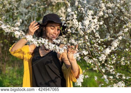An Attractive Girl In A Hat Among Blooming Trees Enjoys The Smell Of Spring Flowers.